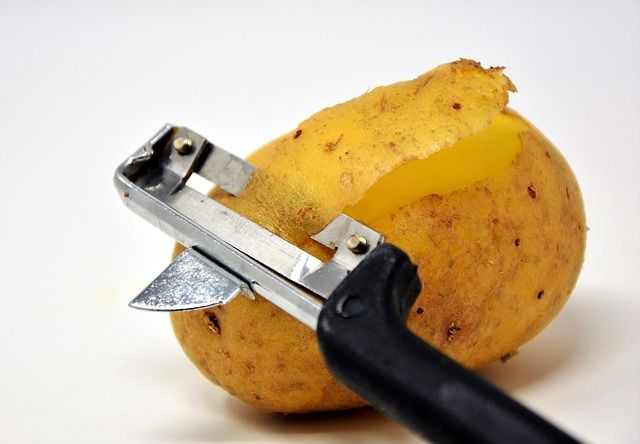 vegetable peel uses a potato being peeled with a hand peeler Kitchen Appliance HQ